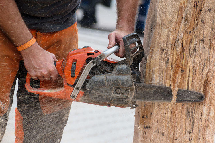Midsection Of Man Cutting Wood With Machinery
