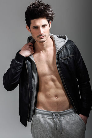 Portrait of athletic man wearing hoodie jacket. Studio shot Abdominal Muscle Adult Beautiful People Body Part Chest Confidence  Fashion Front View Fully Unbuttoned Gray Gray Background Handsome Indoors  Jacket Jeans Leather Looking At Camera Masculinity Muscular Build One Person Portrait Strength Studio Shot Young Adult Young Men