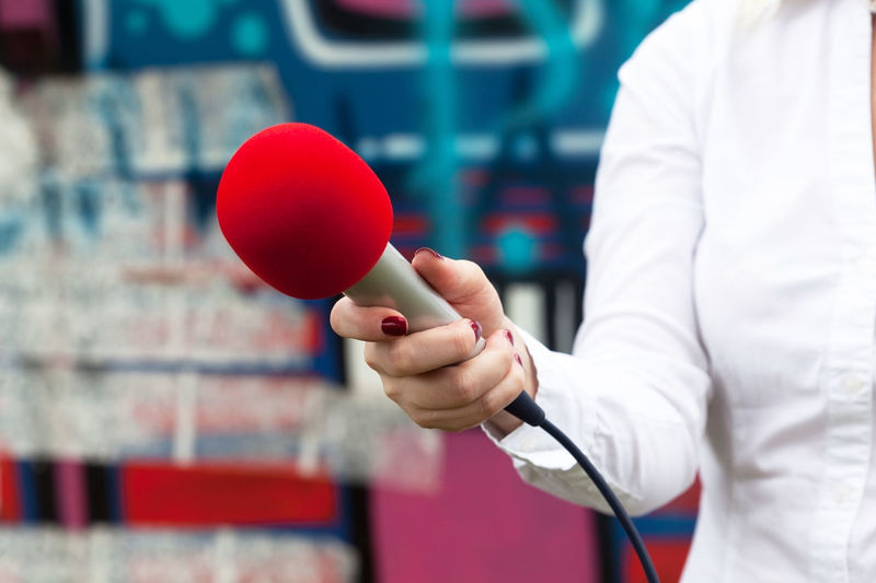 Journalist holding a microphone conducting an TV or radio interview Adult Broadcasting Business Business Finance And Industry Close-up Communication Coneference Day Female Hand Holding Human Body Part Human Hand Indoors  Interview Microphone News Radio One Person People Press Red Reporter