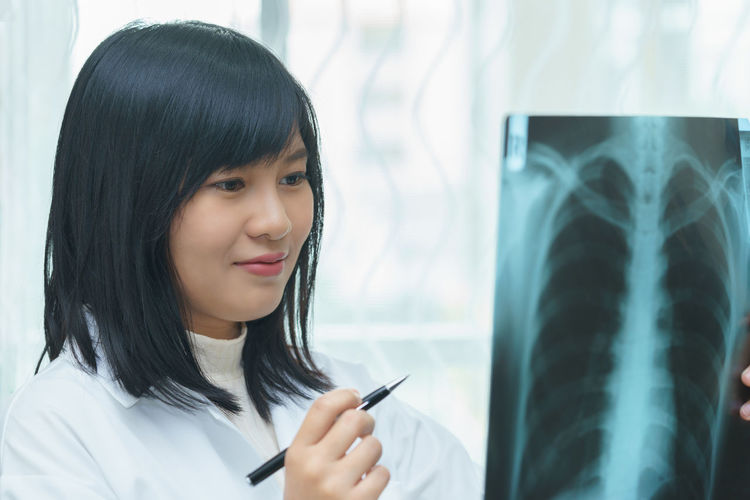 Smiling female doctor examining x-ray image in hospital