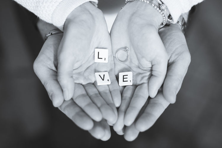 Cropped Hands Of Couple Holding Love Text With Wedding Ring