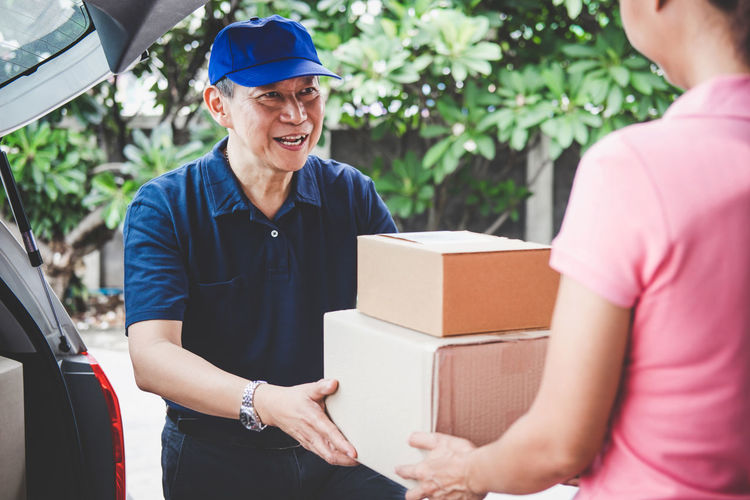 Delivery Postman Sending Adult Box Box - Container Car Cardboard Cardboard Box Casual Clothing Day Emotion Happiness Holding Land Vehicle Mature Men Men Mode Of Transportation Motor Vehicle Outdoors Smiling Standing Transportation Two People Waist Up