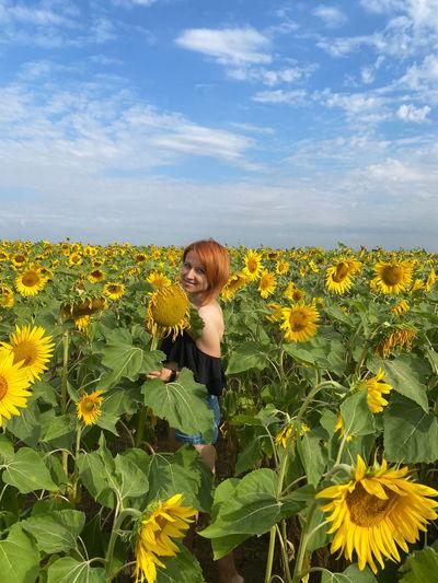 Full length of woman on sunflower field against sky