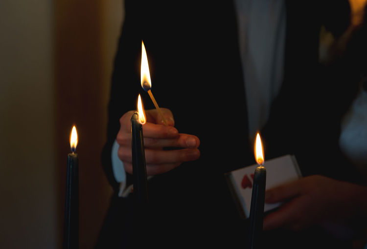 Midsection of person lighting candles with matchstick in darkroom