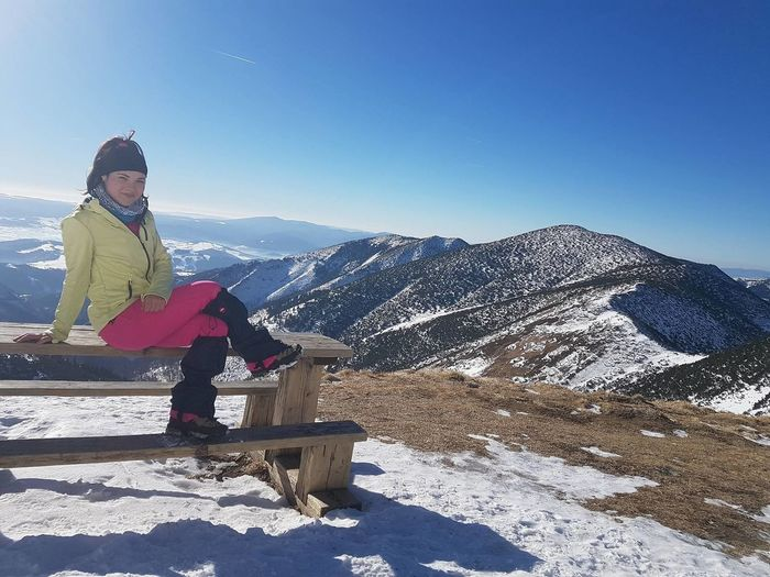 Portrait of young woman sitting on picnic table against tatra mountains during winter