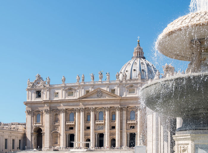 Fountain At St Peter Basilica Against Clear Blue Sky