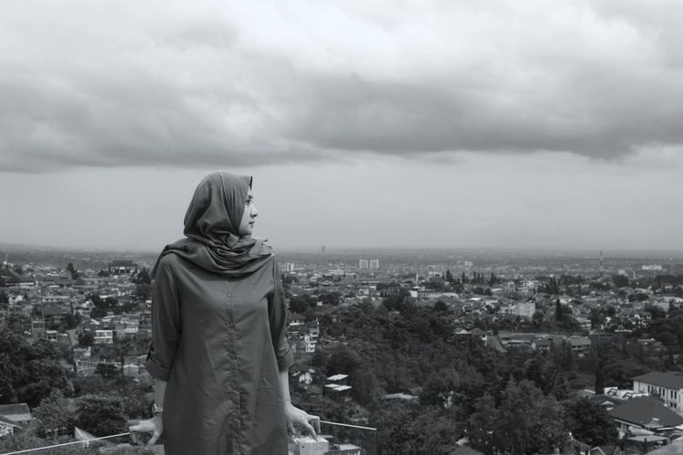 Rear Woman Standing By Cityscape Against Sky