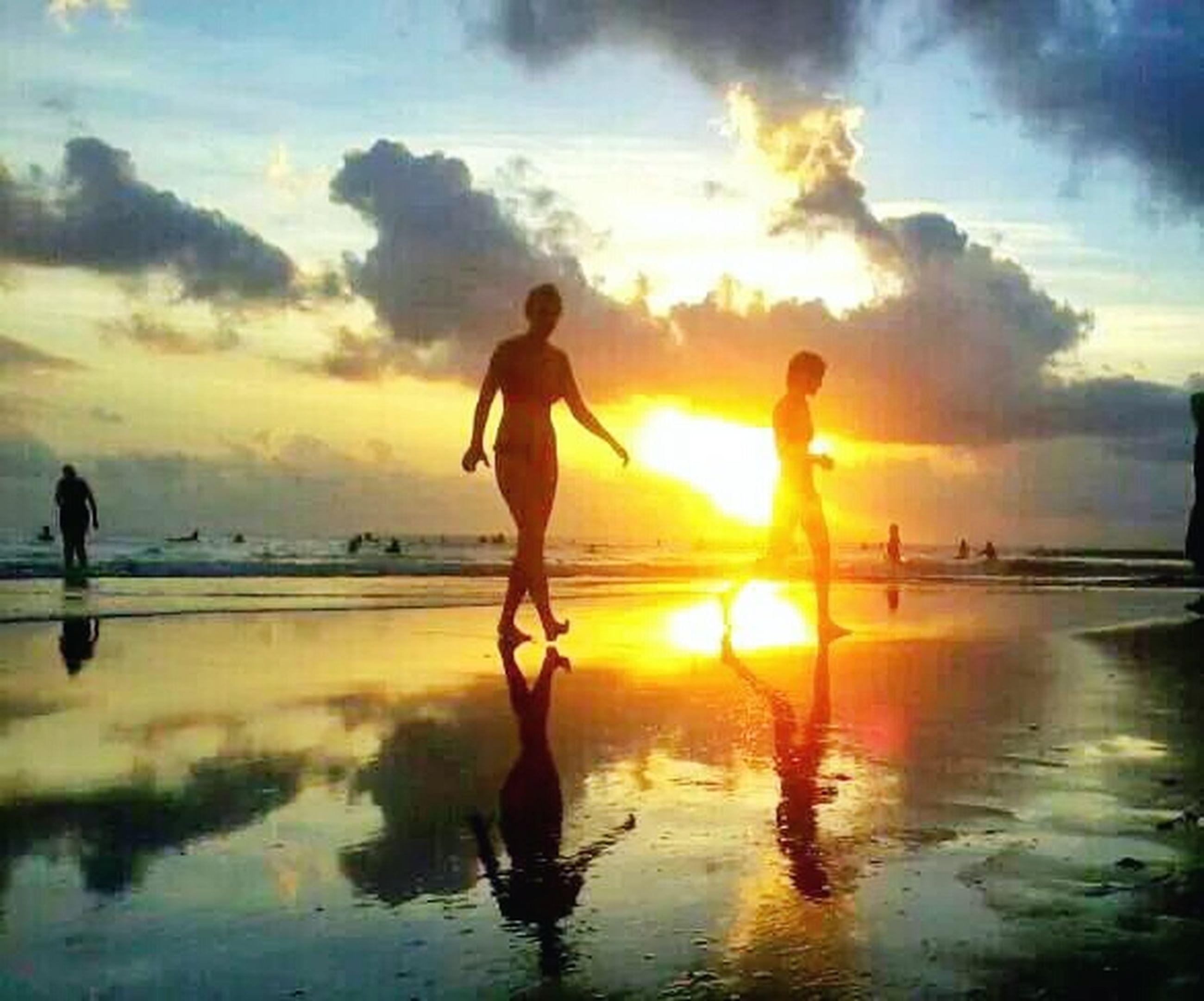 sunset, water, sun, reflection, beach, silhouette, sea, lifestyles, leisure activity, orange color, sky, full length, shore, scenics, horizon over water, boys, childhood, sunlight, standing