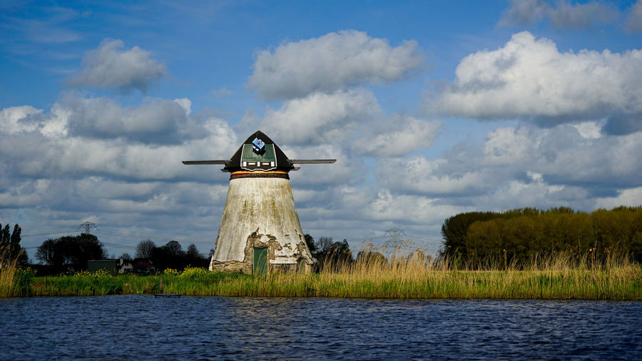 Traditional windmill on field by lake against sky