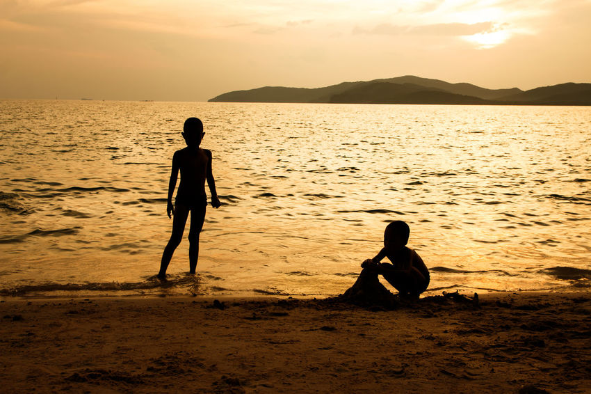 silhouette of people at the beach,The beauty of natural light at sunset. Beach Silhouette Sunset Happiness Happy People Outdoors Holiday Relaxing Children Women Man Romantic Sky Orange Clouds And Sky Love Family Sea Summer Sunrise Boy Freshair Freedom Fun