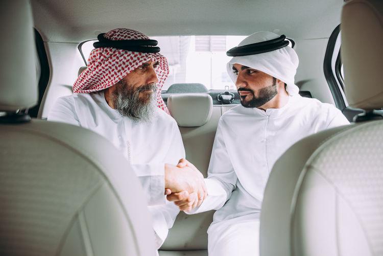 Men wearing dish dash shaking hands while sitting in car