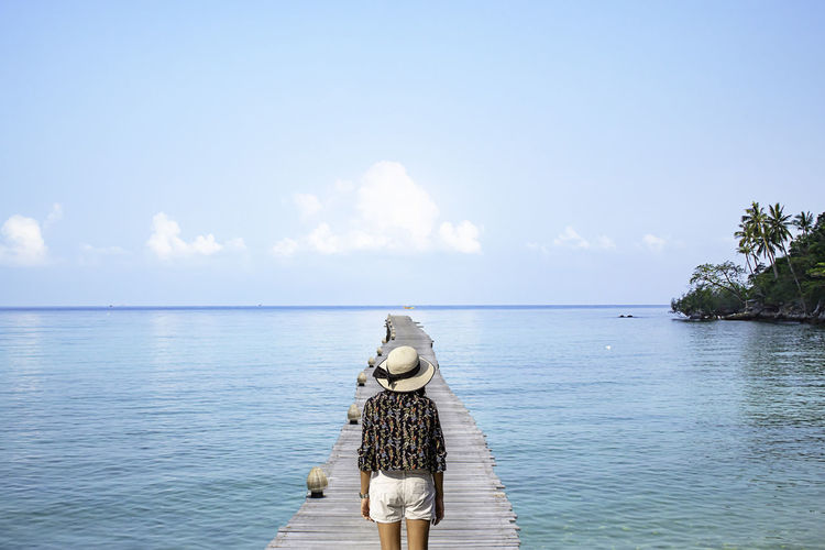 Rear view of woman standing on pier over sea against blue sky