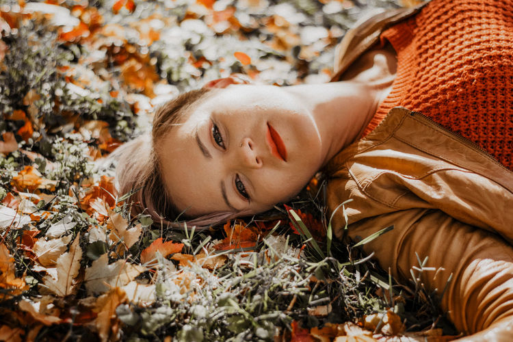 Portrait of woman lying down on autumn leaves