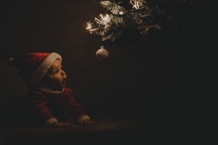 Baby girl looking at illuminated christmas tree at night