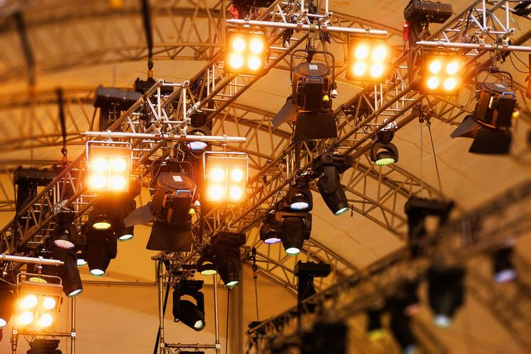 Low angle view of illuminated stage lights at night