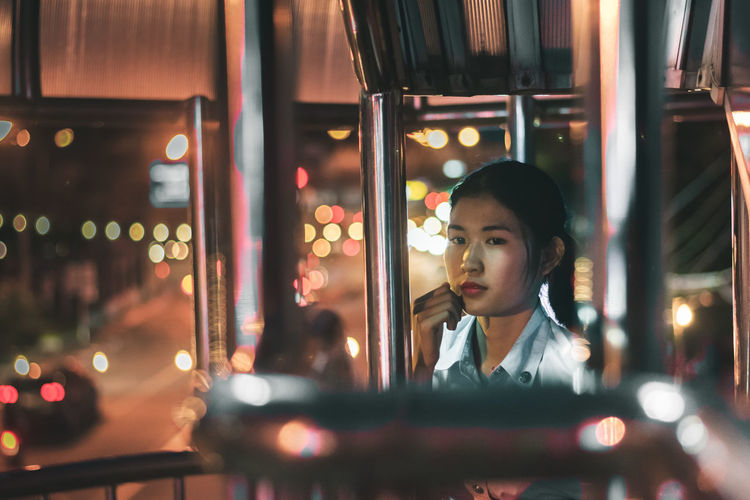 Woman by railing in illuminated city at night