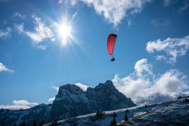 Low angle view of people paragliding on snowcapped mountain against sky