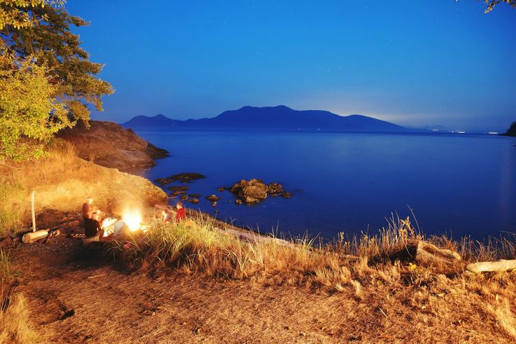 Beach nightlife. Fire Bonfire Beach San Juan Islands Beach Fire Island Life PNW PNWonderland Long Exposure Nightphotography Friends Water Sea Mountain Beach Tree Clear Sky Sky Horizon Over Water Landscape Seascape Calm Ocean Coast Tide Rocky Coastline Entertainment