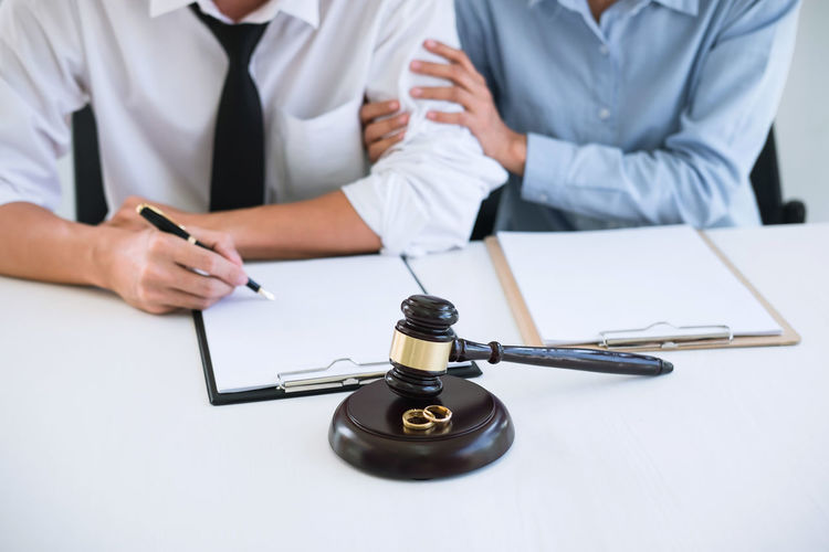 Midsection Of Man And Woman Signing Divorce Papers While Sitting On Table At Courtroom