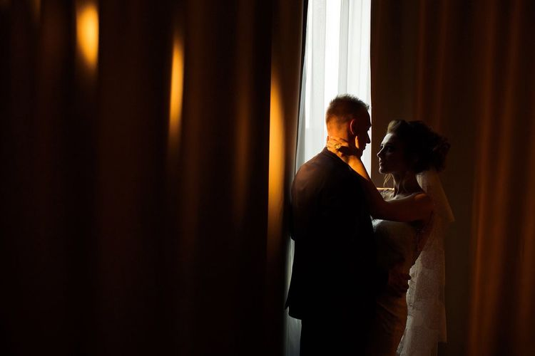 Romantic newlywed couple embracing in room against curtains