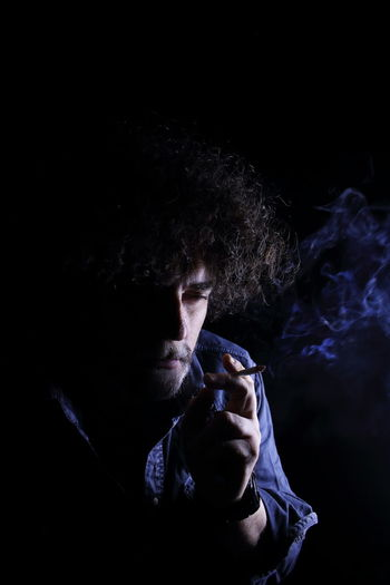 Man Smoking Against Black Background