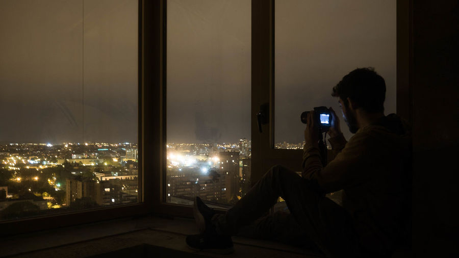 Man Photographing Illuminated Cityscape While Sitting By Window At Night