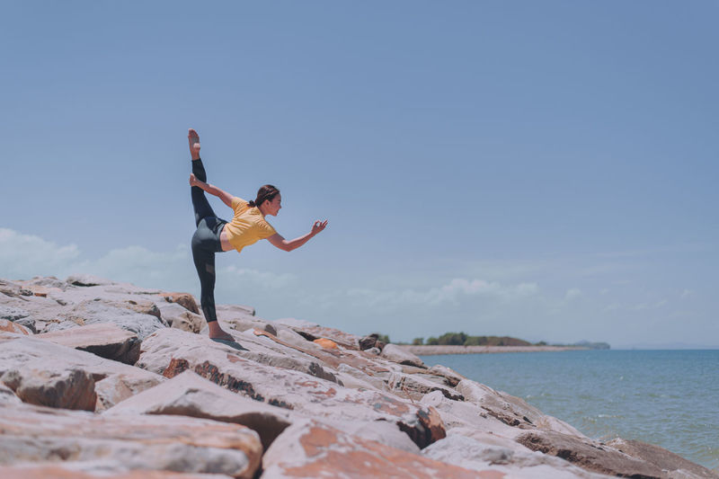 Woman exercising while standing on rock by sea against sky