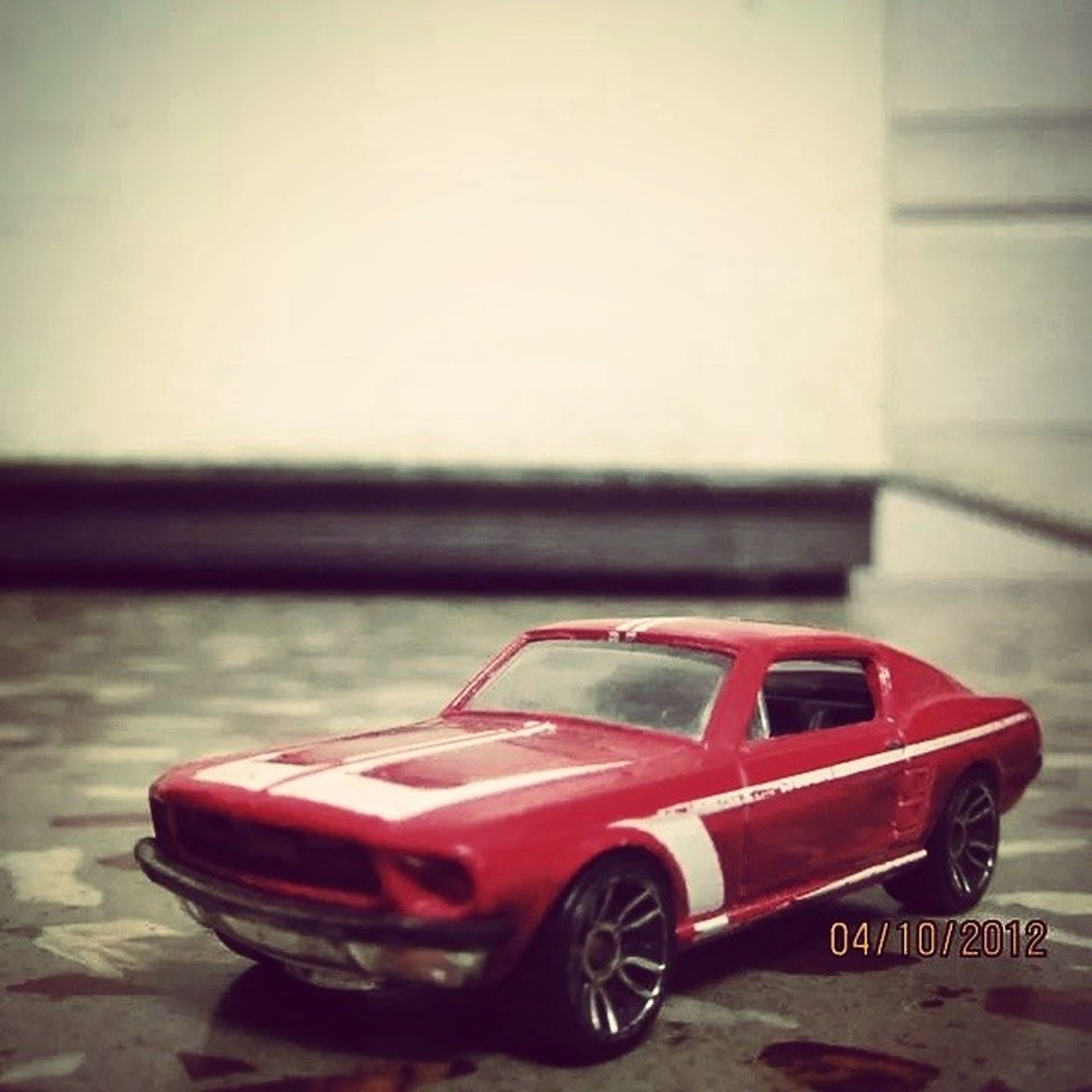 transportation, mode of transport, red, land vehicle, car, close-up, focus on foreground, stationary, no people, day, parked, parking, outdoors, metal, street, part of, wall - building feature, selective focus, road, bicycle
