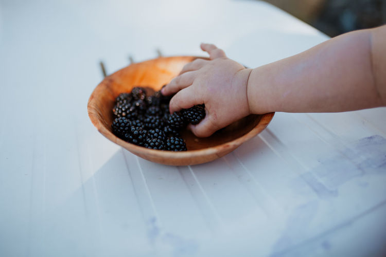 Cropped hand of baby picking blackberries from plate at table