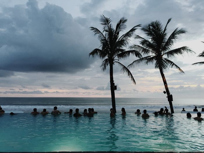 Silhouette people by swimming pool against sky during sunset