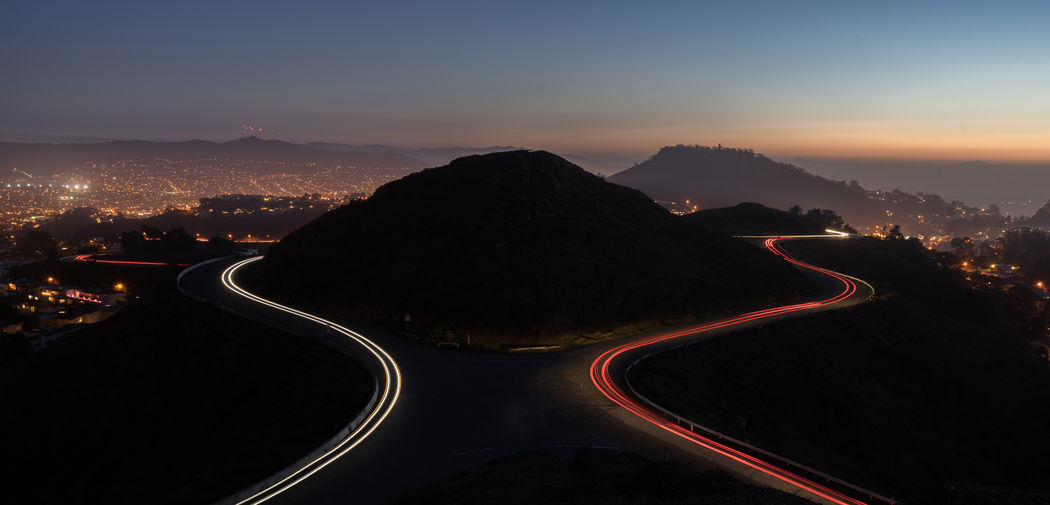 Light Trails On Mountain Road Against Sky At Dusk