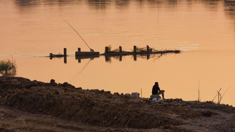 Man sitting against lake during sunset