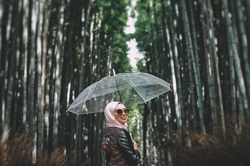 Smiling woman holding umbrella while standing against trees
