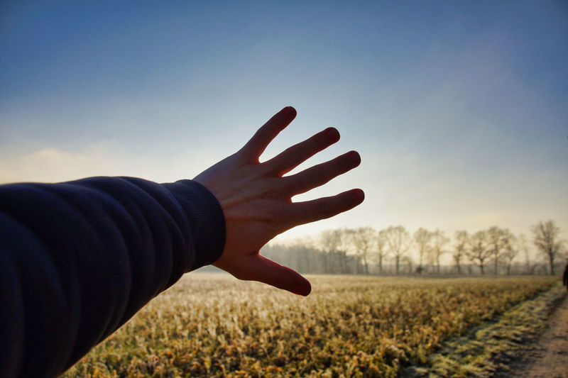 Cropped hand of man blocking sunbeam on field against sky