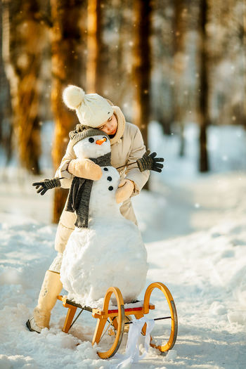 Girl embracing snowman on land during winter