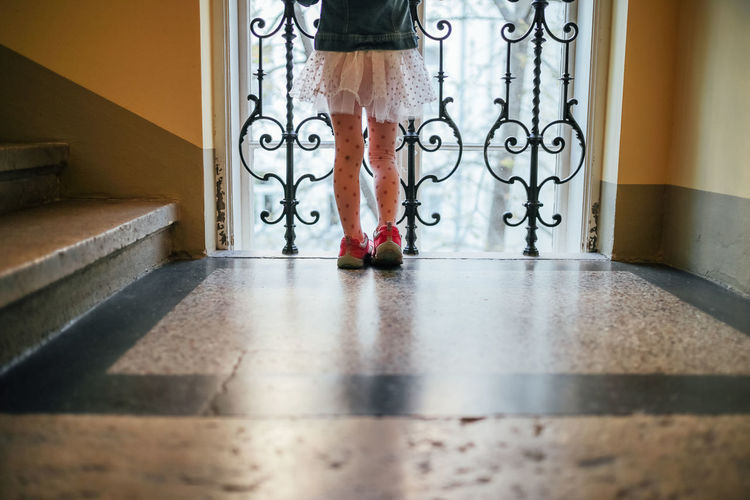 Low section of girl standing by window in corridor