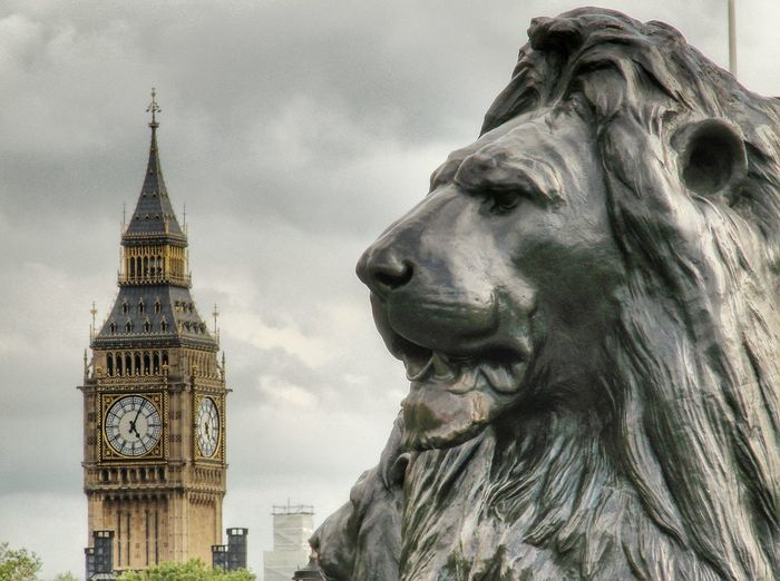 Close-up of lion sculpture with big ben in background against sky