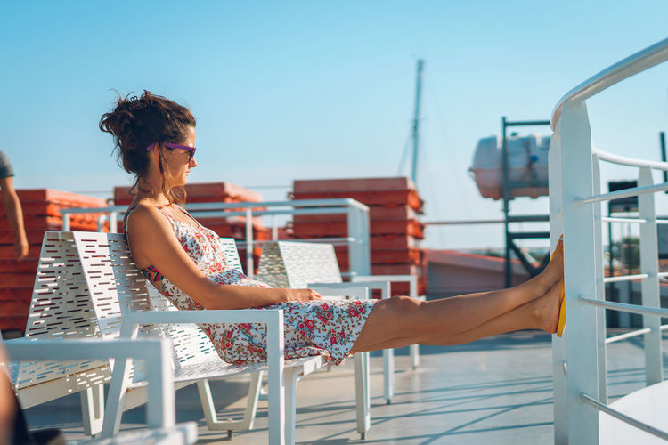 Side view of woman sitting on chair by railing of ship against clear sky