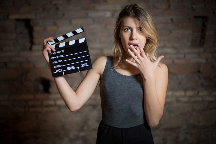 Young blonde actress astonished with movie clapper board Actress Amazed Astonished Audition Beautiful Blonde Cinema Clapboard Clapper Clapperboard Expression Film Girl Looking At Camera MOVIE Pretty Shocked Stage Woman Young