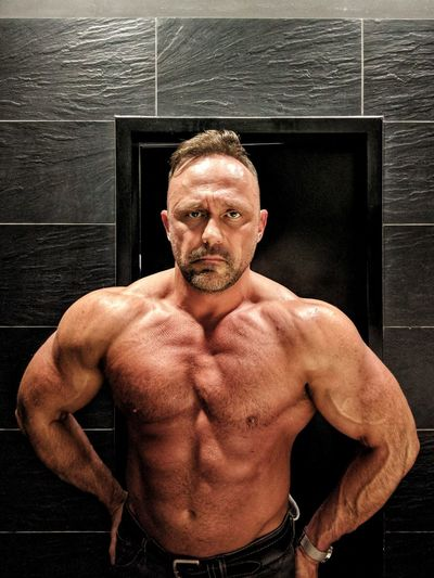 Portrait Of Confident Shirtless Muscular Man Standing Against Wall
