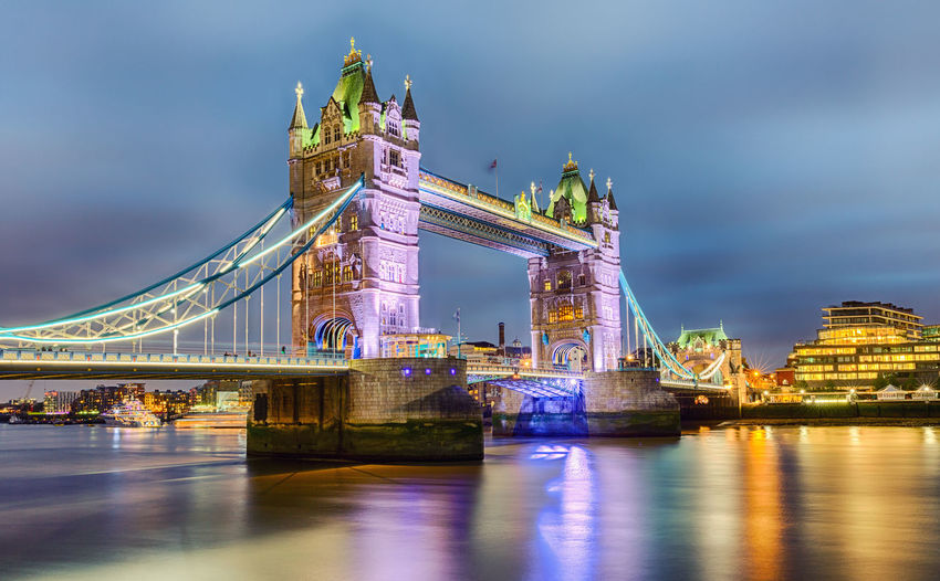 Tower bridge over thames river against cloudy sky in city at dusk
