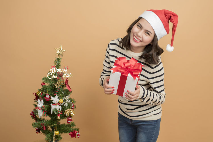 Portrait of young smiling woman with christmas tree
