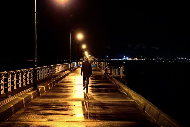 Adult Black Bridge - Man Made Structure City Full Length Illuminated Night One Man Only One Person Outdoors People Pier Street Light Travel Destinations Wet Ground