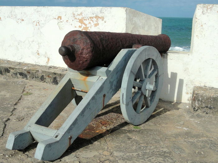 Old rusty cannon by surrounding wall at fortress