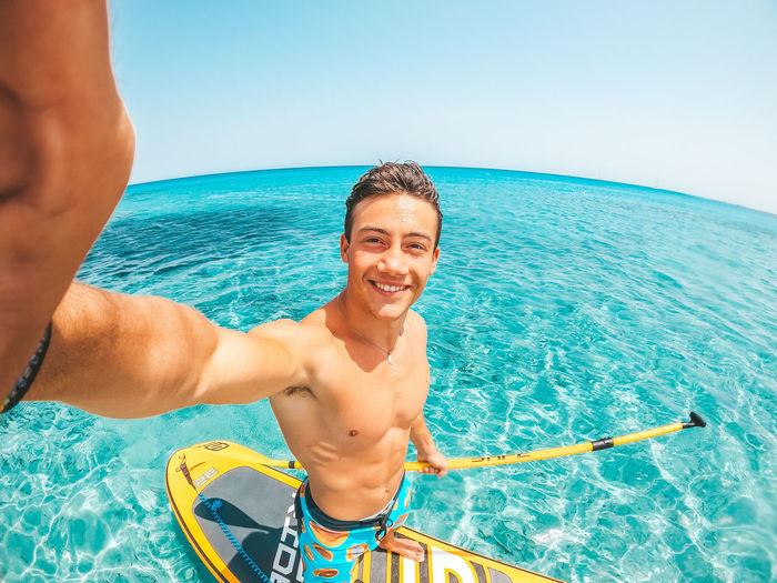 Portrait of smiling man in sea against sky
