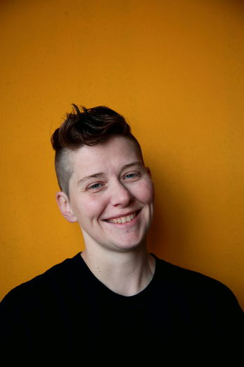 Queer Women Androgynous Androgyny Beautiful Females Gender Masculinity Woman Adult Front View Gay Happiness Headshot Lesbian Lgbt One Person People Portrait Queer Real People Short Hair Smiling Yellow Background