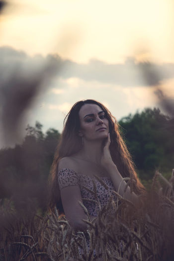 Portrait of young woman on field against sky during sunset