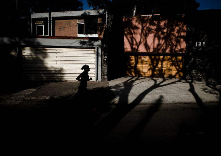 Silhouette person running on street by building