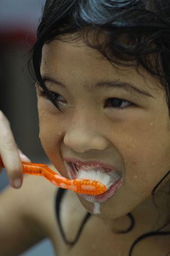 Close-up portrait of girl brushing teeth
