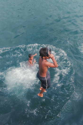 High angle view of shirtless boys playing in sea
